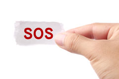 SOS. Hand holding small white paper with text 'SOS' isolated on white background Royalty Free Stock Photography