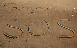 Sos help beach. Writting in the sand on beach. Message saying sos a cry for help Stock Images