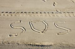 SOS for help on the beach and foot prints. SOS for help written in the sand on the beach, groomer tracks and footprints Stock Images