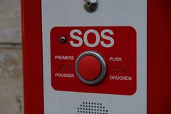 Sos help button. Red multilingual sos help button Stock Photography