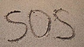 SOS Help Cry For Help Written On Beach Sand stock footage