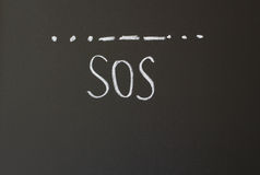 SOS. Inscription in chalk on a blackboard - SOS Stock Photography