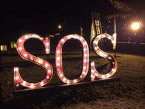 SOS. Lighted SOS sign on the beach in Bali Stock Image