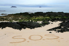 SOS Message. An SOS message written in the sands of a beach stock photo