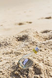 SOS message in bottle on the beach. SOS message in glass bottle on the beach Royalty Free Stock Images
