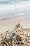 SOS message in glass bottle. On the beach Royalty Free Stock Photos