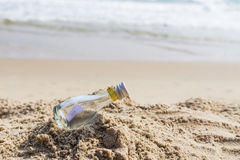 SOS message in glass bottle. On the beach Stock Photo