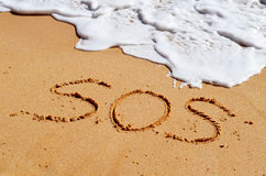 SOS help message in the sand. SOS message written in the sand with a wave coming in Royalty Free Stock Photography