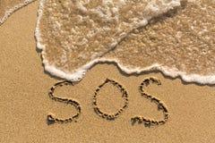 SOS - mot dessiné sur la plage de sable Image libre de droits