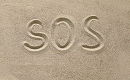 Sos. The name and designation drawn in the sand Royalty Free Stock Photo