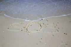 SOS - palabra dibujada en la playa de la arena con la onda suave Foto de archivo