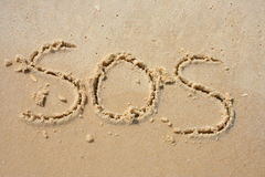 SOS in the sand. SOS written in the sand stock images