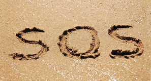 Sos in sand. Sos message written in sand Stock Photos