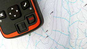 Sos search and rescue. Gps location device over a topo map royalty free stock image