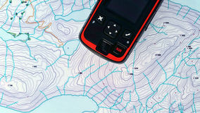 Sos search and rescue. Gps location device over a topo map Stock Image