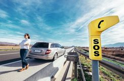 SOS service point on highway. Woman driver has a problem with car Royalty Free Stock Image