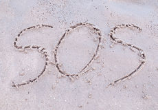 SOS Sign on the beach. SOS(save our souls) drawn on the sand in tropical beach royalty free stock image