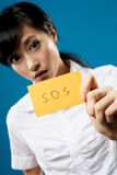 SOS sign. SOS, closeup portrait of Asian business woman on studio blue background Royalty Free Stock Photo