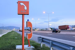 SOS sign and emergency telephone on the road. Emergency telephone on highway in the evening time Stock Photography
