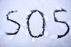 SOS sign for help needed written in the snow.  Stock Image