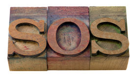 Sos sign in letterpress type. Call for help - SOS word in vintage wooden letterpress printing blocks, isolated on white Stock Photo