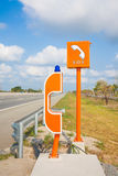 SOS sign and phone box on highway, road safety Stock Images