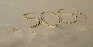 SOS sign in sand. Fun SOS sign written in sand stock photos