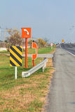 SOS. Sign and telephone on roadside of motorway for traveler in case of trouble, evening sunlight Stock Photos