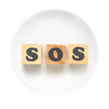 SOS sign. White plate with sign SOS composed of wooden blocks. Bad food concept - isolated on a white background Stock Image