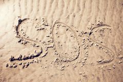 Sos sign write on sand. Sos sign write by hand on sand stock images