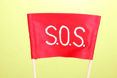 SOS signal written on red cloth. On green background Royalty Free Stock Photography