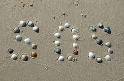 SOS signalerar på sanden som göras från, beskjuter royaltyfri fotografi