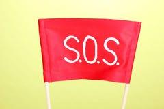 Sos-signalering som skrivs på den röda torkduken royaltyfri fotografi