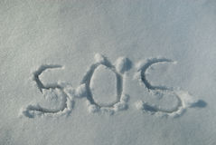 SOS in Snow. The familiar SOS call for help scribed by finger into undisturbed snow Stock Images