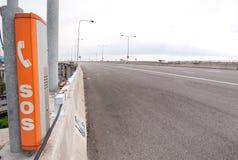 Sos-tecken och telefonask på huvudvägen Arkivbild
