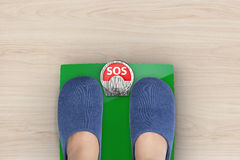 "Sos with weight scale. Foot standing on weight scales with text ""sos Stock Photo"
