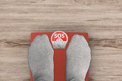 "Sos with weight scale. Foot standing on weight scales with text ""sos Stock Image"