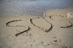 SOS - word drawn on the sand beach with the soft wave.  royalty free stock image