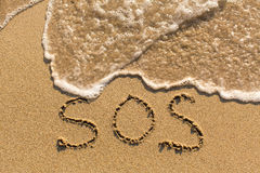 SOS - word drawn on the sand beach. With the soft wave Royalty Free Stock Image