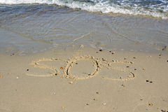 SOS - word drawn on the sand beach with the soft wave. Stock Image