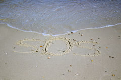 SOS - word drawn on the sand beach with the soft wave. Stock Photo