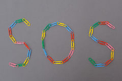 Sos word made of paper clips isolated. Sos word made of paper clip isolated Royalty Free Stock Photos