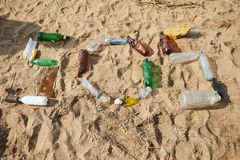 SOS word made of plastic bottles. From above SOS word made of rubbish plastic bottles on sand royalty free stock photo