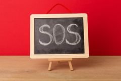 Sos word written on school blackboard. Against red background. Emergency concept, copy space stock photo