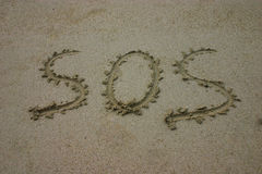 SOS written in sand. SOS written by hand in sand on the beach Stock Photo