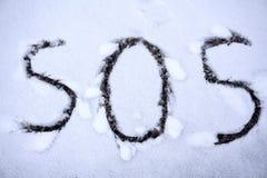 SOS znak dla pomocy potrzebował pisze w śniegu obraz stock