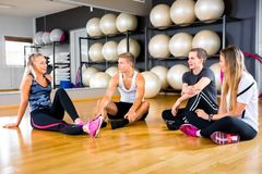 Sosial sprawności fizycznej treningu drużyna odpoczywa na podłodze przy gym centrum zdjęcia royalty free