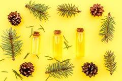Sosna istotny olej w butelkach na żółtego tła odgórnym widoku Wzór z sosna rożkiem i gałąź Fotografia Stock