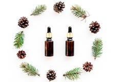 Sosna istotny olej w butelkach na białego tła odgórnym widoku Wzór z sosna rożkiem i gałąź Fotografia Royalty Free