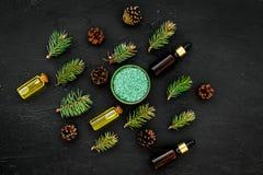 Sosna istotny olej w butelkach na ciemnej tło odgórnego widoku kopii przestrzeni Wzór z sosna rożkiem i gałąź Fotografia Royalty Free